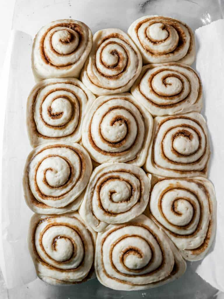 Fully proofed cinnamon rolls in a baking pan, ready to go in the oven
