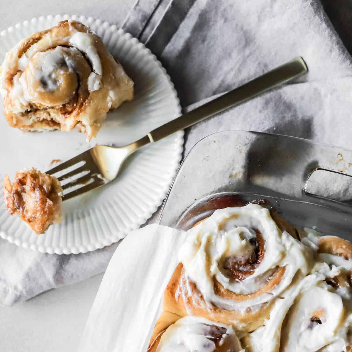 Warm cinnamon rolls with icing in a glass pan