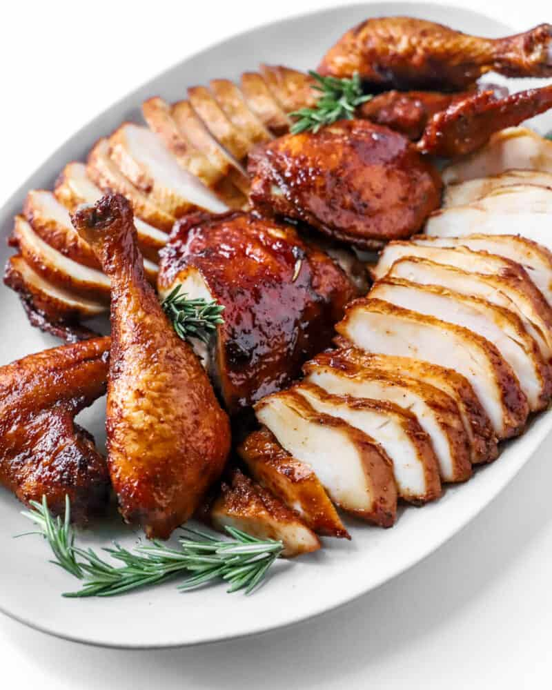 sliced chicken on a serving platter with rosemary sprigs