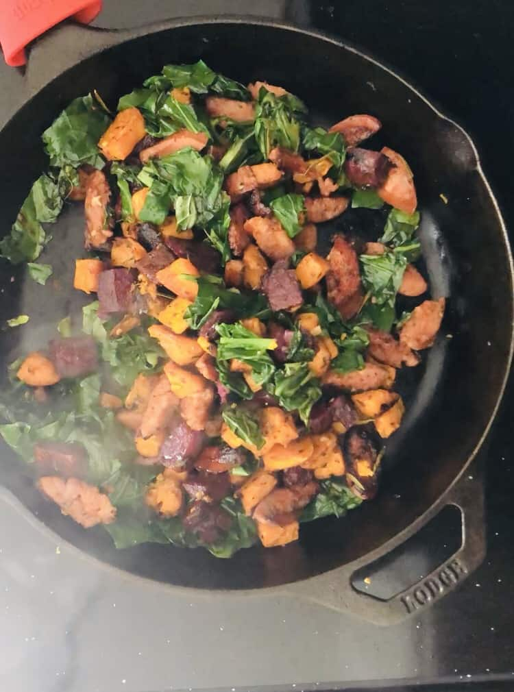 potatoes, kale and sausage sautéing in a skillet