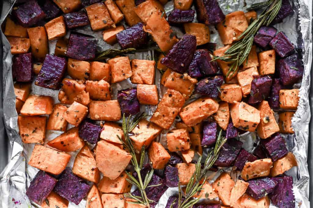 Colorful orange and purple sweet potatoes, roasted on a sheet pan with rosemary