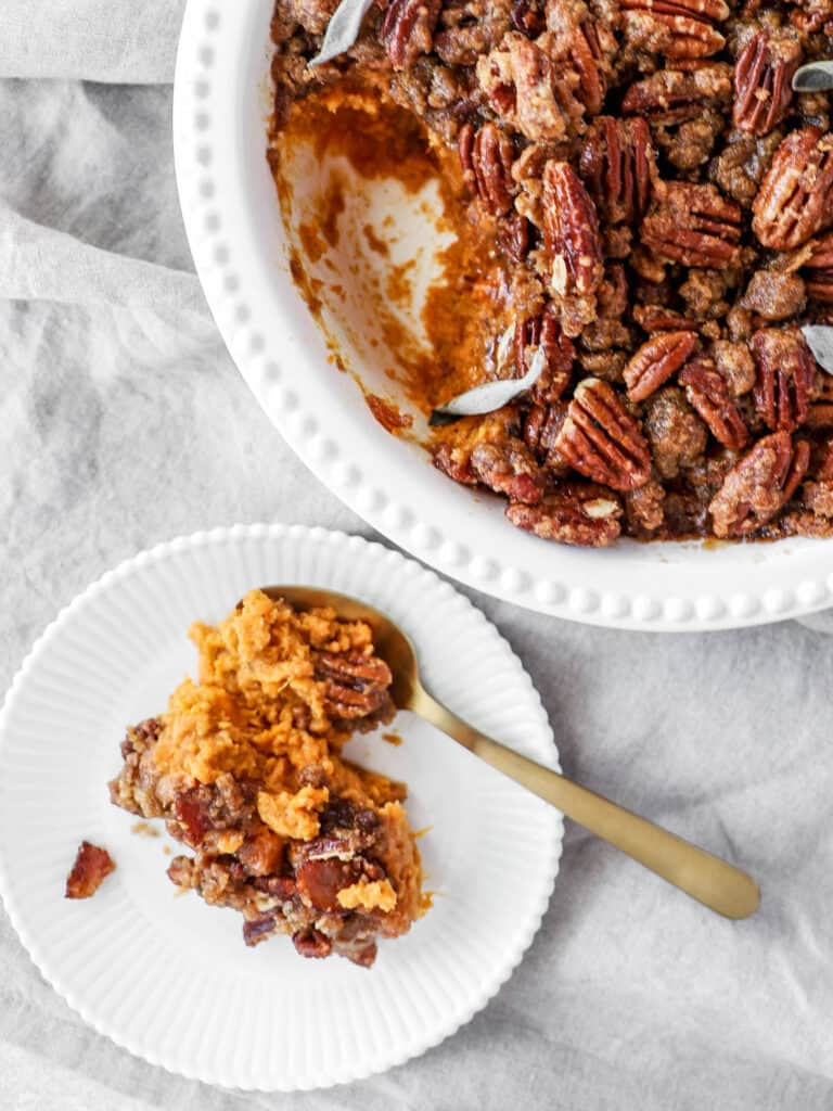 Sweet potatoes with a layer of pecans in a casserole dish