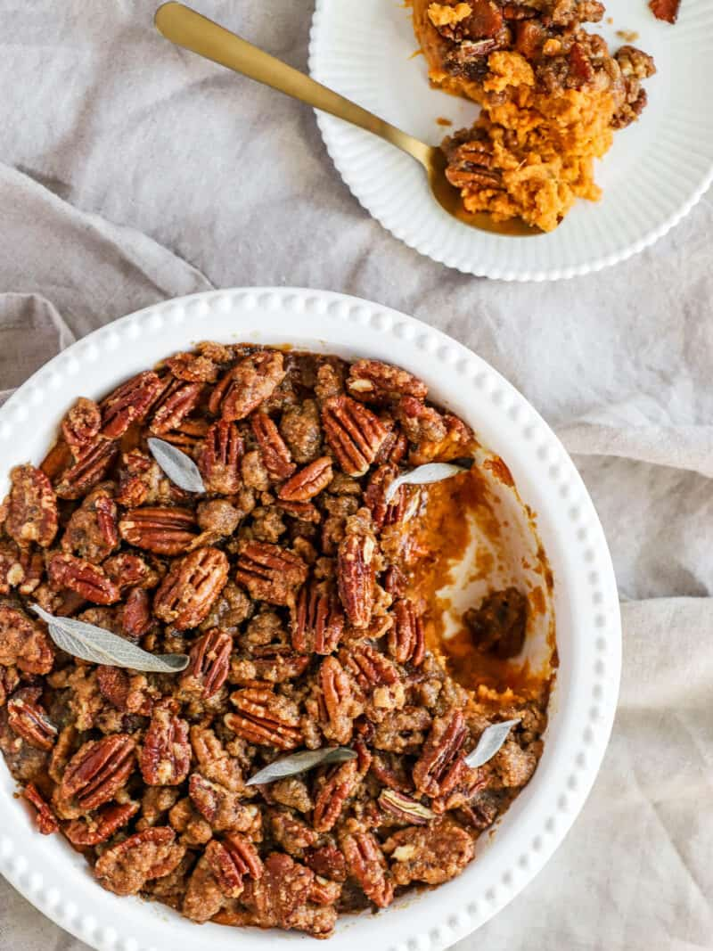 sweet potatoes layered with pecans in a casserole dish
