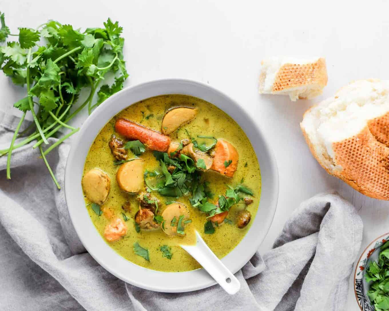 vietnamese chicken curry recipe, Ca Ri Ga, in a bowl with soup spoon and bread on the side