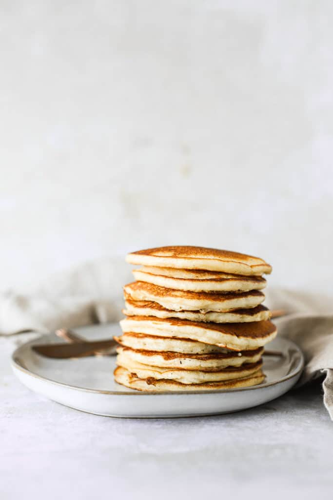 buttermilk pancakes on a plate with maple syrup