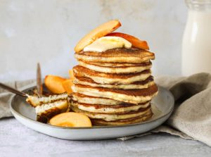 buttermilk pancakes on a plate with peaches and maple syrup